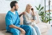 Fotografie mladý ošetřovatel pohledu na usmívající se starší žena mluví o smartphone