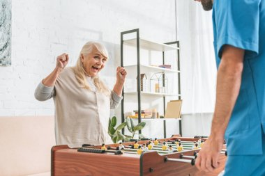 cropped shot of male nurse and excited senior woman playing table football