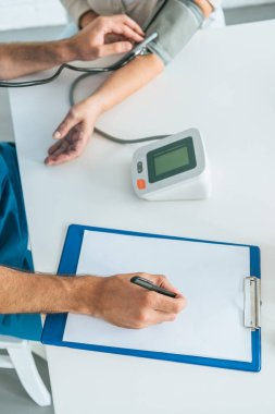Cropped shot of male nurse writing on clipboard while measuring blood pressure to senior woman stock vector