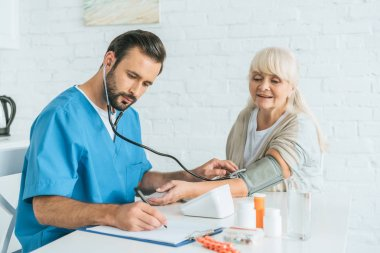 male nurse in stethoscope writing on clipboard while measuring blood pressure to senior woman