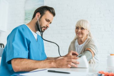 low angle view of male nurse measuring blood pressure to smiling senior woman