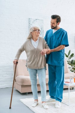 full length view of male nurse supporting senior woman in eyeglasses with walking stick