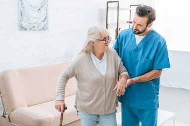 male nurse supporting senior woman in eyeglasses with walking stick