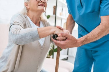 cropped shot of male nurse helping senior woman with walking cane