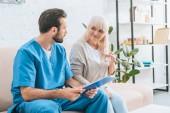 Fotografie mladý ošetřovatel drží schránky a při pohledu na usmívající se starší ženou