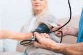 close-up partial view of nurse measuring blood pressure to senior woman