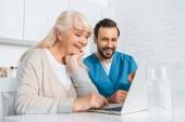 Lächelnde junge Betreuerin und glückliche Seniorin benutzen gemeinsam Laptop
