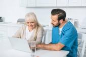 Junge männliche Sozialarbeiter und lächelnde ältere Frau mit Laptop zusammen