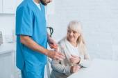 Fotografia ritagliata colpo di assistente sociale dando bicchiere dacqua e le pillole alla donna maggiore