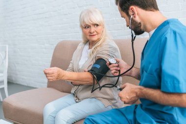social worker measuring blood pressure to senior woman sitting on couch