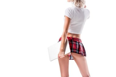 partial view of woman in seductive schoolgirl uniform with laptop isolated on white
