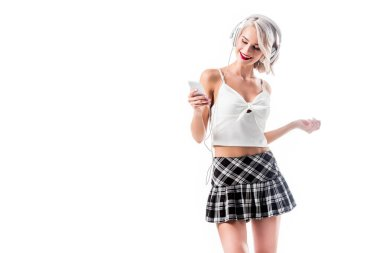 portrait of seductive schoolgirl with smartphone listening music in headphones isolated on white