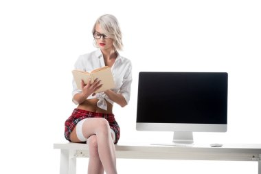 blond seductive schoolgirl in short plaid skirt reading book while sitting on table with blank computer screen isolated on white