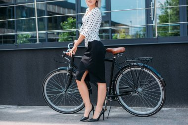 Cropped shot of businesswoman in stylish clothing with retro bicycle standing on street stock vector