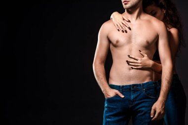 partial view of woman hugging shirtless boyfriend in jeans isolated on black