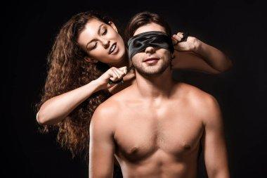 Portrait of woman tying silk ribbon on boyfriends eyes isolated on black stock vector