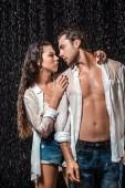 Fotografie Porträt von sexy Paar in weißen Hemden stehen unter Regen isoliert auf schwarz