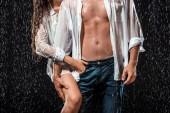 Fotografie Teilansicht des sexy Paar in weißen Hemden stehen unter Regen isoliert auf schwarz