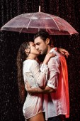 boční pohled na romantický pár v bílých košilích s deštníkem stojící v dešti na černém pozadí
