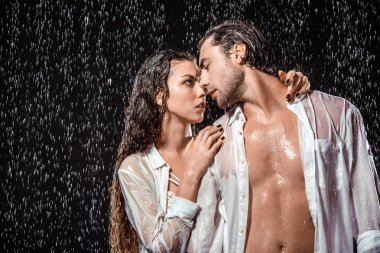 portrait of sexy couple in white shirts standing under rain isolated on black