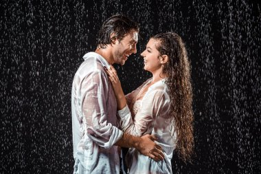 side view of smiling couple hugging while standing under rain isolated on black