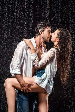 seductive wet couple in white shirts standing under rain isolated on black