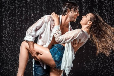 smiling wet couple in white shirts standing under rain isolated on black