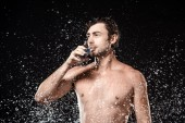Photo portrait of shirtless man drinking water from glass while swilled with water isolated on black