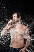 portrét shirtless chlap pitné vody ze skla, zatímco vypláchla s stříkající vodě, izolovaný na černém pozadí