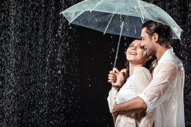 Side view of romantic couple in white shirts standing under umbrella under raindrops isolated on black stock vector