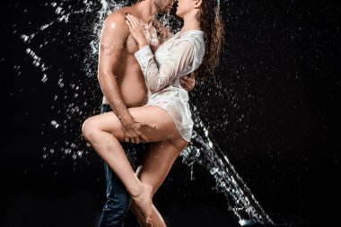 partial view of seductive couple swilled with water isolated on black