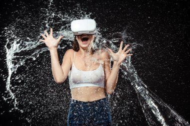 portrait of emotional woman in vr headset swilled with water isolated on black