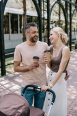 laughing parents holding coffee to go near baby carriage in park