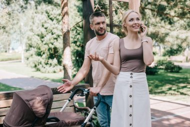happy mother talking by smartphone near baby carriage in park, irritated father looking at her