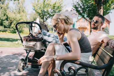 mother smoking cigarette near baby carriage in park and talking by smartphone