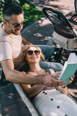 wife lying on husband legs near baby carriage in park and holding book