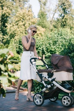 mother in sunglasses walking with baby carriage in park and talking by smartphone