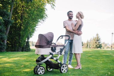 parents hugging near baby carriage in park
