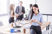 Selektivní fokus asijské podnikatelka pomocí smartphone a jeho kolegové za v kanceláři