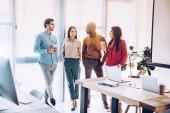 Skupina lidí multikulturní obchodní bavit během přestávky na kávu v kanceláři