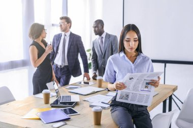 selective focus of asian businesswoman reading newspaper and colleagues having conversation behind in office