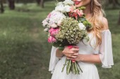 cropped shot of tender smiling blonde bride holding wedding bouquet outdoors