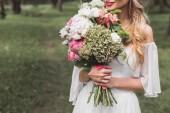 Fotografie cropped shot of tender smiling blonde bride holding wedding bouquet outdoors