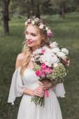 Fotografie krásná usměvavá mladá nevěsta v květinový věnec drží svatební kytice a koukal venku