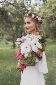 krásná usměvavá mladá nevěsta drží svatební kytice a koukal v parku