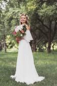 Fotografie krásná šťastná mladá nevěsta drží svatební kytice a usmívá se na kameru v parku