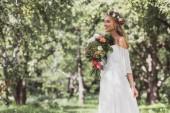 Fotografia bella giovane sposa felice holding bouquet matrimonio e che osserva via nel parco