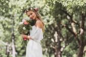 Fotografia bella giovane sposa in corona floreale che tiene il mazzo di fiori e sorride alla macchina fotografica