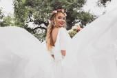 Fotografie nízký úhel pohled šťastné blonde nevěsta ve svatebních šatech a květinový věnec se usmívá na kameru v parku