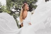 Fotografie nízký úhel pohled šťastné blonde nevěsta ve svatebních šatech a květinový věnec koukal v parku